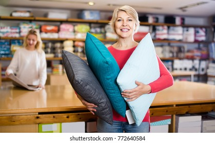 positive aged woman enjoying purchased home textiles in textile shop
