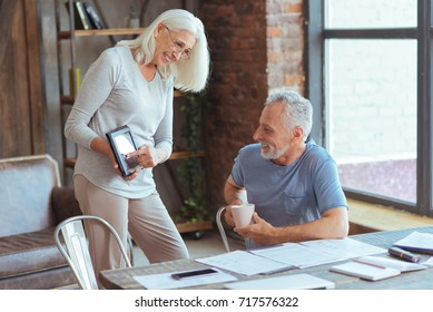 Positive aged woman pointing the screen of the tablet