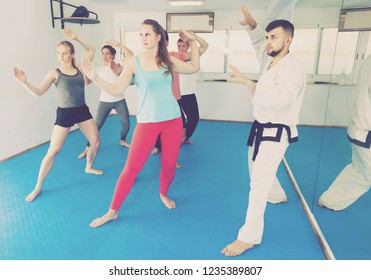 positive american adults attempting to master new moves during karate class