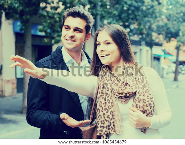 Positive american  brunette showing direction to Indian guy at the street