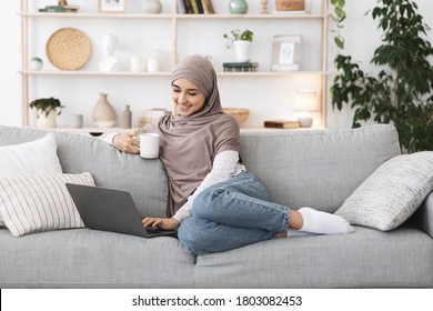 Positive arabic woman unwinding with laptop and coffee on couch at home, relaxing in stylish living room