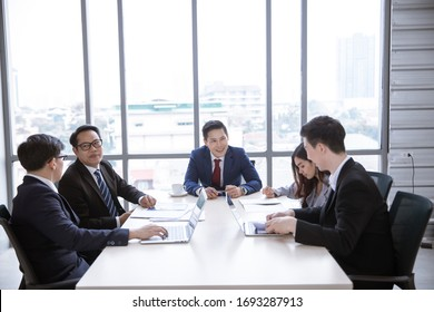 Positive Asian business team having meeting in office.