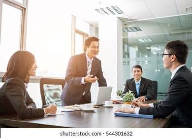 Positive Asian business team having meeting in office
