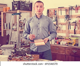 Positive attractive adult man  working with  wood  at workplace