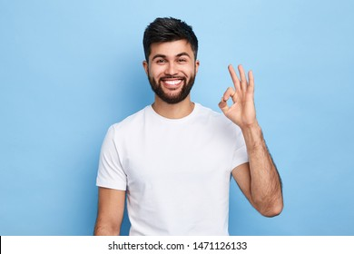 positive attractive Arab young man showing ring gesture with fingers.close up portrait, good job, agreement concept. I am OK, approval. studio shot.guy being satisfied with suggestion
