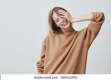 Positive attractive blonde young model wears casual loose sweater, being happy to receive good news. Joyful woman rejoices weekends, relaxing indoors, isolated against gray background