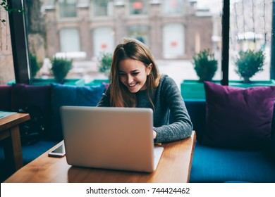 Positive attractive hipster girl with long hair chatting with friends and reading funny information on internet websites sitting at modern laptop computer device in stylish coworking space