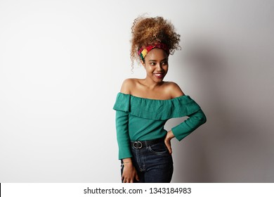 Positive attractive young black african female with Afro hairstyle, points aside with cheerful expression, isolated over bright light backgroud. Advertisement and ethnicity.