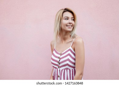 Positive attractive young woman with blond hair with blue beautiful eyes with a sweet smile in a trendy summer striped sundress walks around the city near a vintage pink building. Cheerful girl model.