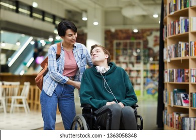 Positive attractive young woman with satchel pushing wheelchair and talking to disabled student in library