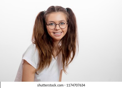 positive awesome young woman with blue eyes in eyeglasses and white T-shirt looking at the camera. close up portrait. copy space