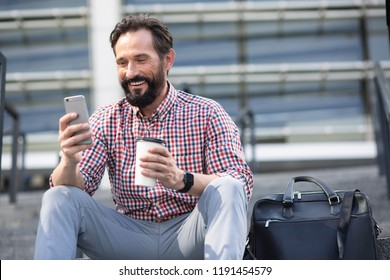 Positive bearded adult man sitting in urban settings while drinking coffee and using phone