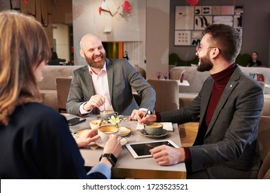 Positive bearded businessman in jacket laughing while drinking coffee with business partners in modern restaurant