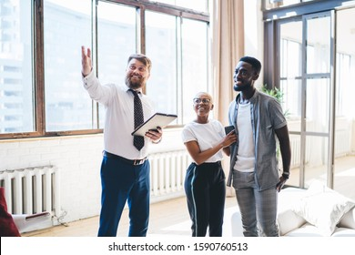 Positive bearded chubby man in formal outfit with clipboard showing living room to smiling amused ethnic couple while standing at modern sunny apartment