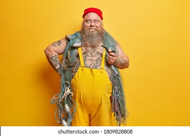 Positive bearded fisherman ready for fishing, holds smoking pipe, wears red hat and overalls, enjoys favorite hobby, poses against yellow background. Funny experienced sailor ready for marine travel.