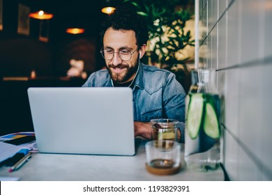 Positive bearded hipster student watching funny tutorial online in earphones connected to laptop device sitting in cafe.Young man laughing while reading news on website and enjoying music via app