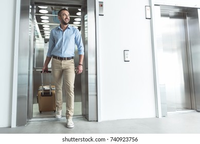Positive bearded man is getting out of elevator