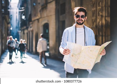 Positive bearded tourist in holding travel map in hands while strolling on narrow streets of architectural city and enjoying travel lifestyle.Young man lover of trips walking in urban setting