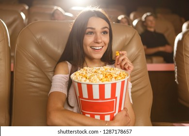 Positive and beautiful dark haired girl enjoying watching interesting film at cinema. Pretty female viewer in white shirt and jeans looking at screen, keeping popcorn and smiling.