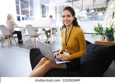 Positive beautiful young woman with badge sitting in comfortable bean bag and smiling at camera, while typing on laptop, she working in cozy office