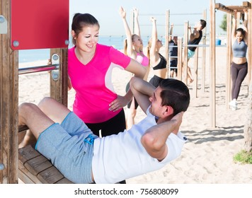 positive belorusian  people leading healthy lifestyle, doing exercises on ocean beach at daytime