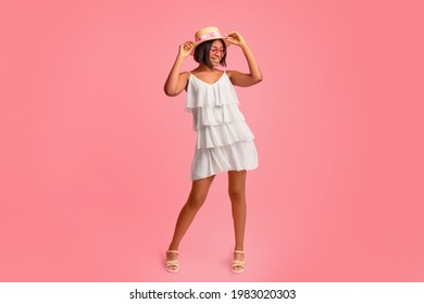 Positive black lady in fashionable summer clothes having fun, laughing and posing over pink background in studio, full length portrait. Cheerful African American woman dressed for hot season