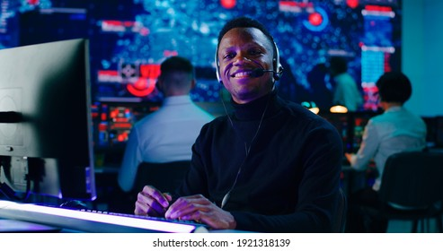 Positive black male programmer in headset using computer then smiling and looking at camera while working in office of high tech security center