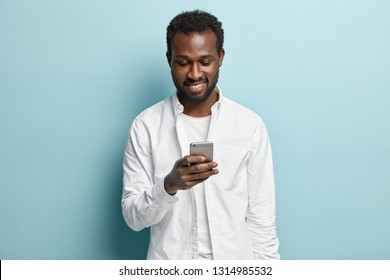 Positive black man with toothy smile, looks at smartphone, reads text message from friend, good news, wears white shirt, models in studio against blue background. Spare time and technology