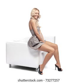 Positive blonde woman stting on a white leather couch.