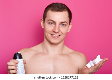 Positive blue eyed man carries bottle of shaving gel, poses with naked torso, showsc bare shoulders, muscles, has gentle smile, has smooth sking after shaving, isolated over pink background.