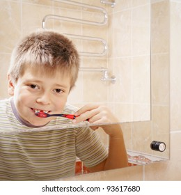 Positive boy brushing teeth reflection in mirror