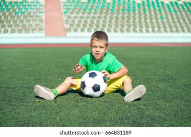 Positive boy child playing football on the field.