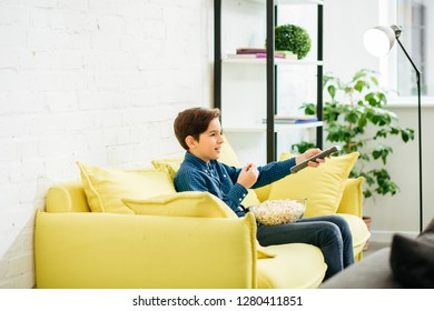 Positive boy using remote control and switching TV channels while sitting on the yellow sofa with a bowl of popcorn on his laps
