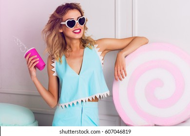 Positive  bright portrait of cute pretty woman holding  pink cocktail  and posing   near huge colorful props, colorful fake  lollipop  sweets in  pastel  blue stylish summer outfit. Candy girl .
