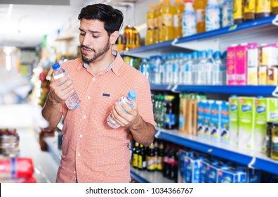 positive brunette man is consumering bottles with water in hypermarket.