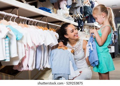 Positive brunette mother with daughter buying kids clothes in blue color in shop