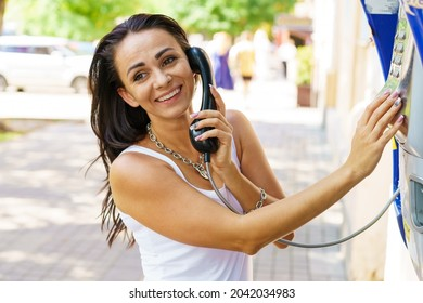 Positive brunette woman holding telephone receiver calls through stationery phone in street, tourist talking on payphone working with coins, happy with international communication on sunny summer day