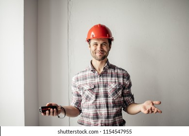 positive builder with tool in hands greeting his in the construction.close up portrait