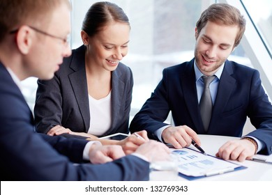 Positive business people analyzing financial aspects of their work