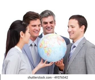 Positive business team looking at a terrestrial globe against a white background