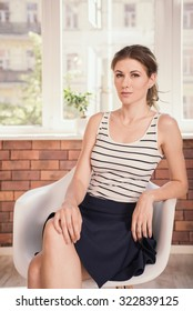 Positive business woman sitting on the chair and looking at camera