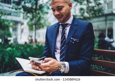 Positive businessman dressed in stylish formal wear laughing during online chat on smartphone device.Smiling proud ceo sitting on bench and reading funny sms message on modern mobile phone