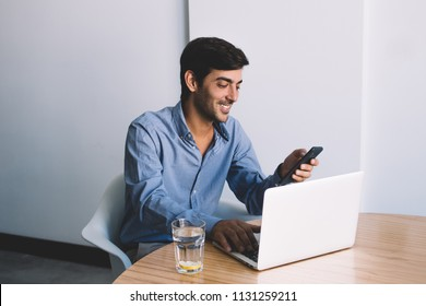 Positive businessman enjoying break of work sitting at office and chatting with friends via cellular connection, happy man checking notification at smartphone after searching information on laptop