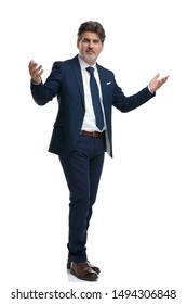 Positive businessman greeting with his arms wide open while wearing a blue suit and standing on white studio background