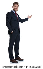 Positive businessman presenting and holding his hand in his pocket while laughing and wearing a blue suit, standing on white studio background