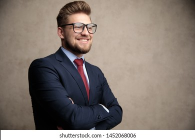 Positive businessman smiling with his hand folded and looking away while wearing glasses and a blue suit, standing on wallpaper background