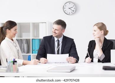 Positive businesspeople sitting beside desk in light office