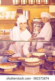 Positive cafe staff offering fancy and sponge cakes for dessert