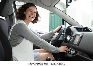 Positive car driver starting vehicle engine. Young woman happy about new car purchase. New car concept