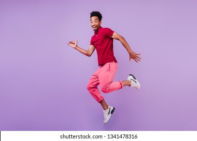 Positive carefree african man in sport shoes dancing on purple background. Handsome glad guy in pink pants jumping with smile.
